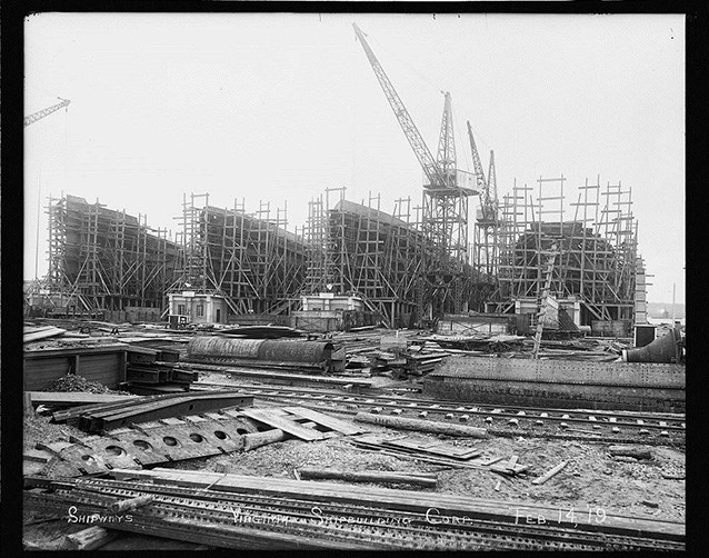 Ships surrounded by scaffolding being built in a shipyard