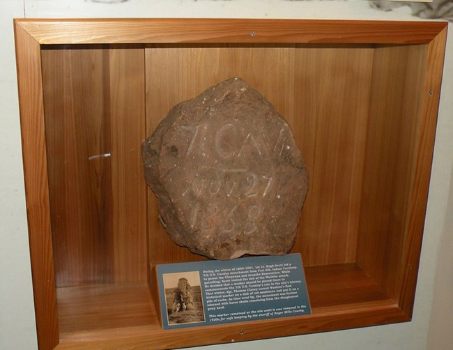 A large stone inside a glass case on a wall.