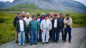 A group of 14 men stand on a gravel road in front of a mountain.