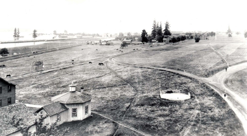 Black and white photo of Vancouver Barracks with open fields and some buildings.