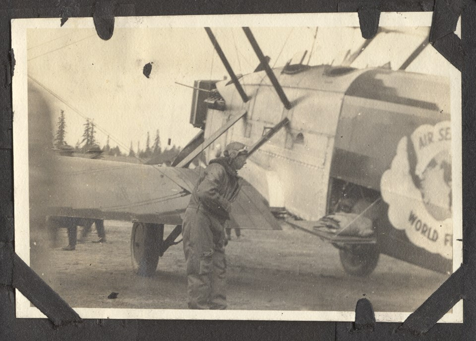 Photo of man in flight suit standing next to a biplane aircraft