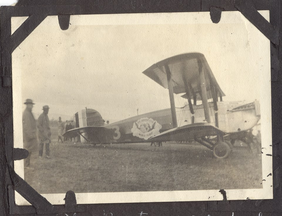 Black and white photo of biplane aircraft. A group of people stand behind the aircraft.