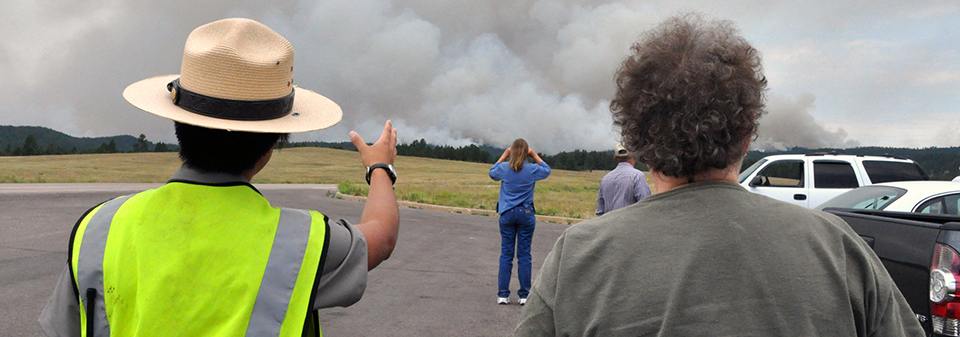 A ranger points to a smoke plume while standing next to a man.