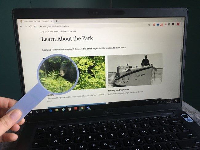 Laptop computer screen with Pictured Rocks National Lakeshore's 'Learn About the Park' page displayed on it