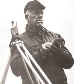 Glaciologist William O. Field holds pencil and notepad next to surveying tripod. Black and white image.