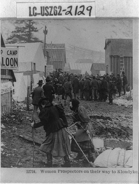 A group of people head to the Klondike, with two women pulling a sled of supplies