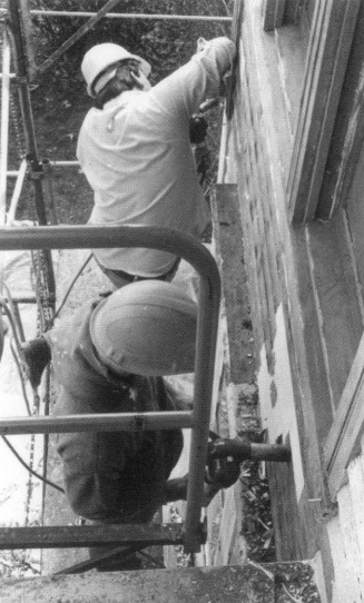 Two men on scaffolding removing paint from a wall.