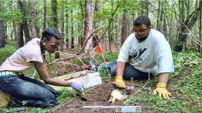 Two people doing archaeology in a forest