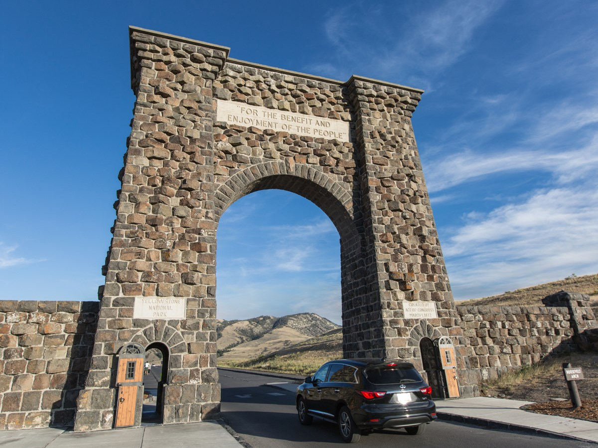 Car passing under a stone arch at Yellowstone