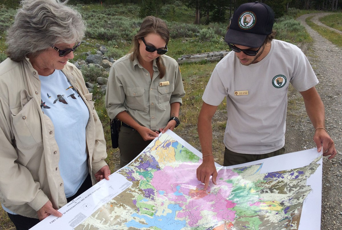 people examining a geologic map