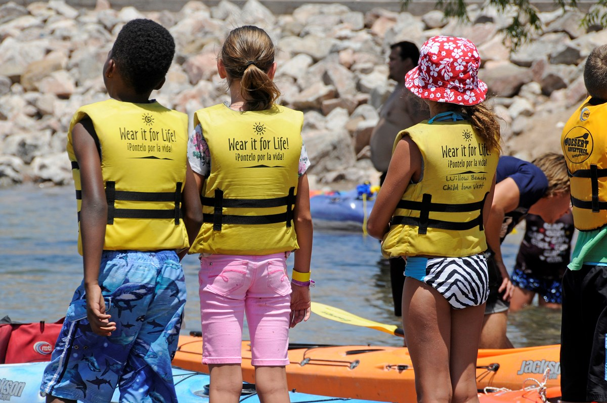Kids standing near water and kayaks wearing life jackets
