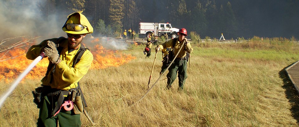 A firefighter sprays a hose attached to a wildland fire engine in the distance.