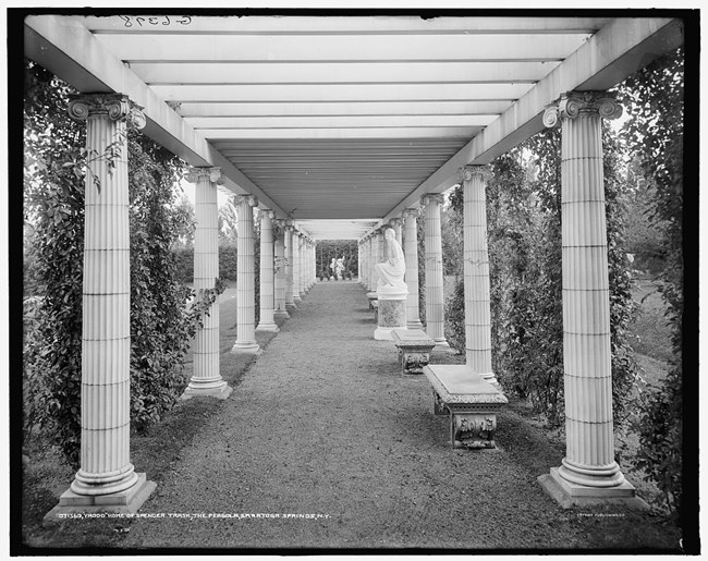 View along the pergola with columns lining a walkway