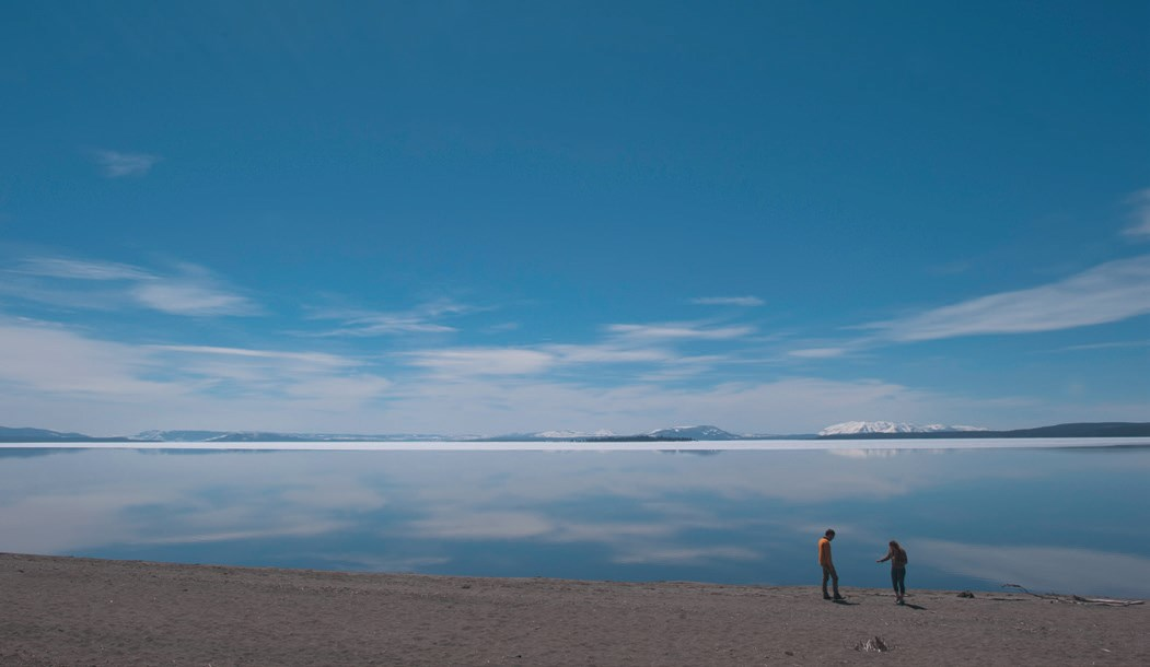 Two people on the beach of a very large lake with snow-capped mountains in the background.
