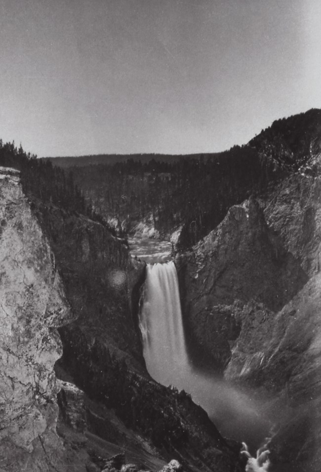 Black and white image of a large waterfall.