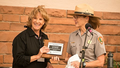 Superintendent Kate Cannon hands a plaque to CNHA Executive Director Roxanne Bierman