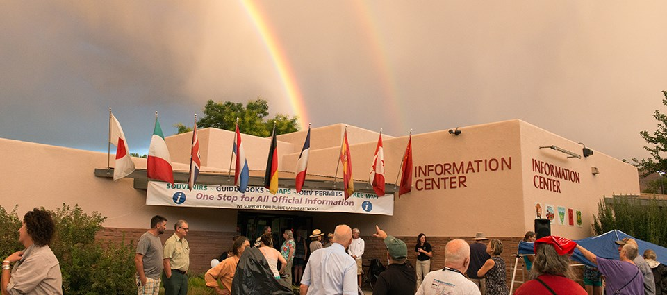 "a group of people stands outside a building reading ""Information Center."" A rainbow is overhead."