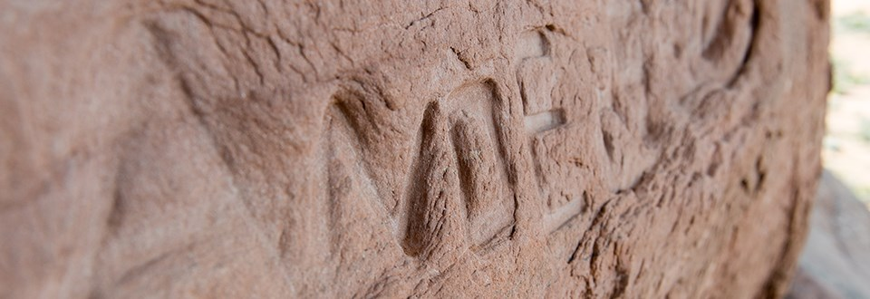 carved letters in a sandstone surface