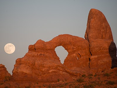 the full moon rises above a reddish stone arch