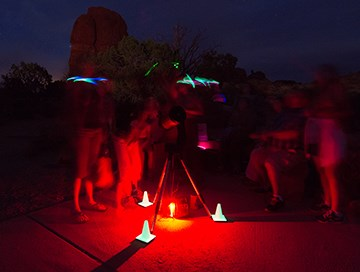 a tripod is illuminated with red light at its base as shapes of people move around it