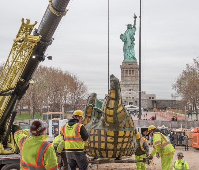 The original torch being lifted by crane with the Statue of Liberty in the background.