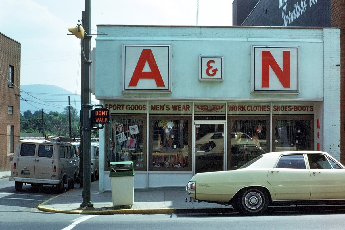Historic view of a mid-century storefront and car