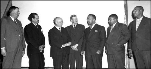 3 African American men in suits on the right stand next to a group of white men in suits
