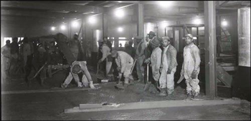 african american workers in overalls inside building