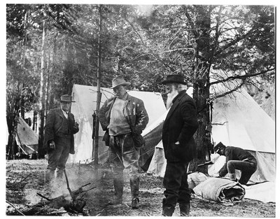 Black and white photo of Teddy Roosevelt standing with other men around a smoldering pile of branches
