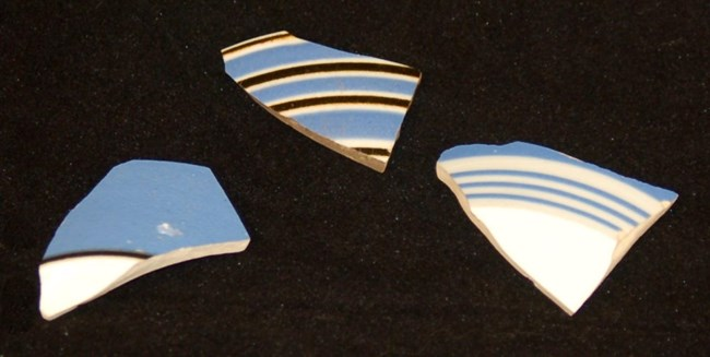 Photo of three fragments of bandedware with blue, black, and white colored bands.