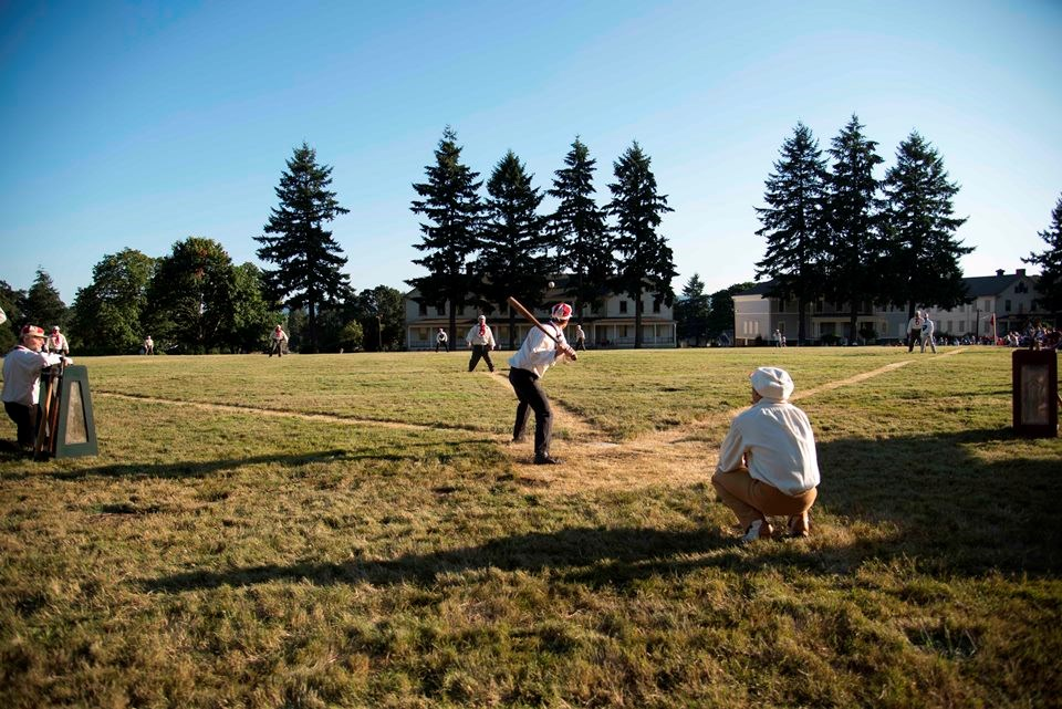 Photograph taken from behind home plate as costumed base ball players play at Vancouver Barracks