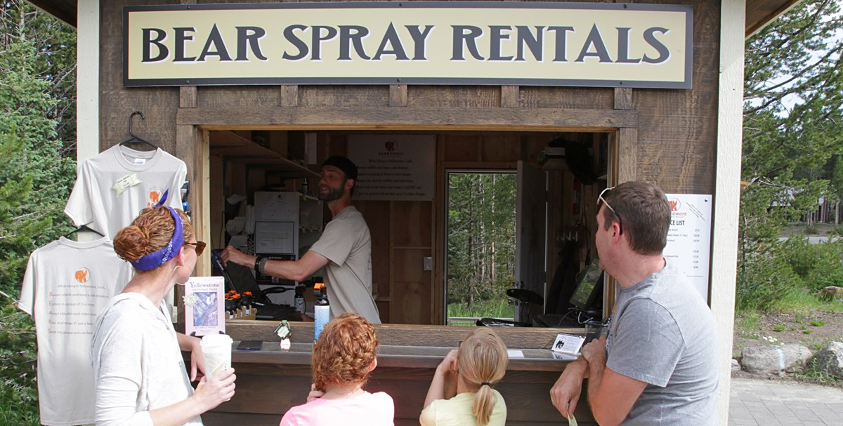 "A family of 4 stand at a booth with a sign that reads ""Bear Spray Rentals"""