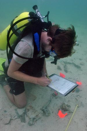 [photo] SCUBA diver writing on tablet at underwater archeological site.
