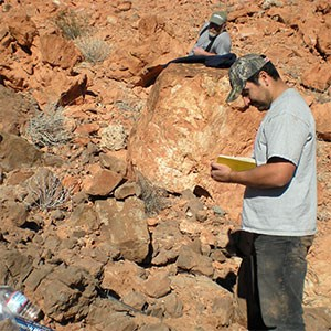 scientist taking notes at rock outcrop