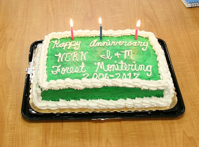 A sheet cake with candles reads: Happy Anniversary, NCRN I&M, Forest Monitoring 2006-2017