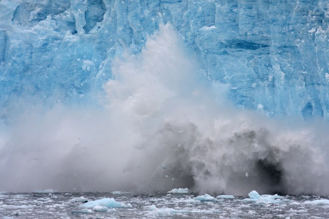 Chunks of ice fall into the ocean off the front of a glacier.