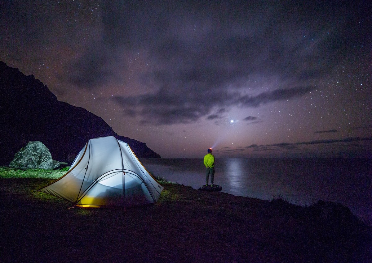 man camping at a lake at night