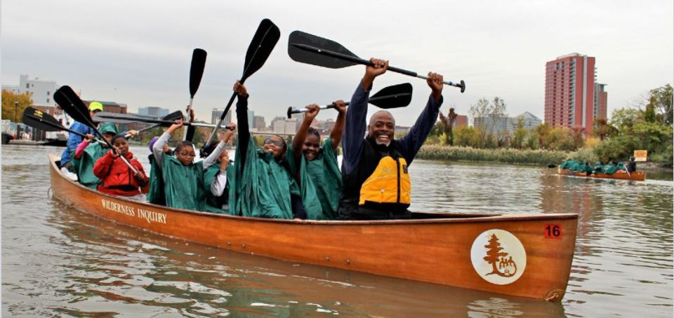 Man and students in canoe on urban river