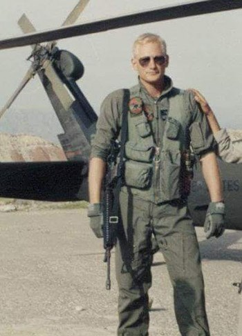 Bill Bouley, in military uniform stands in front of a helicopter