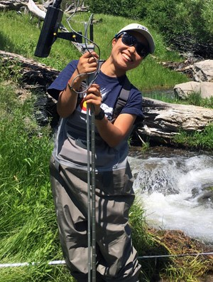Intern holding equipment next to mountain stream