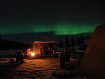 the northern lights dance over people sitting around a fire