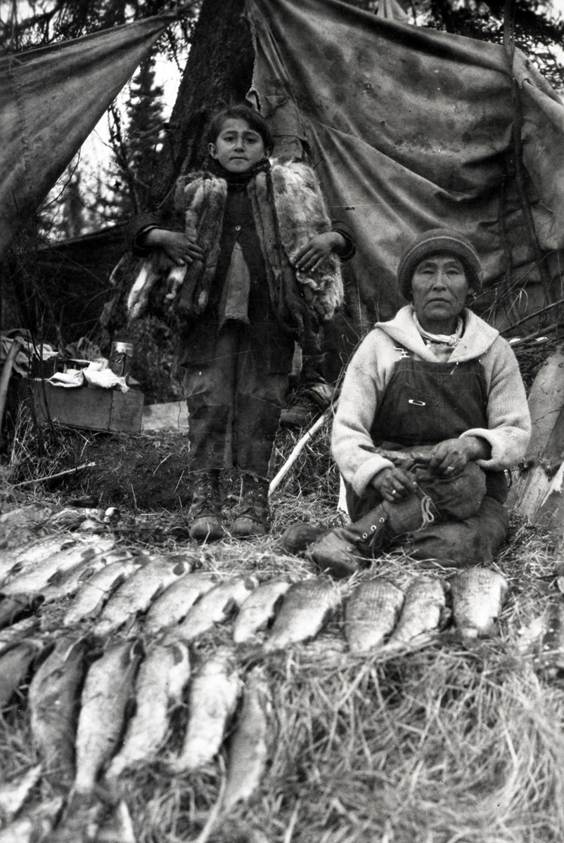 Historic photo of a woman and child in front of tent with fish and furs in foreground.