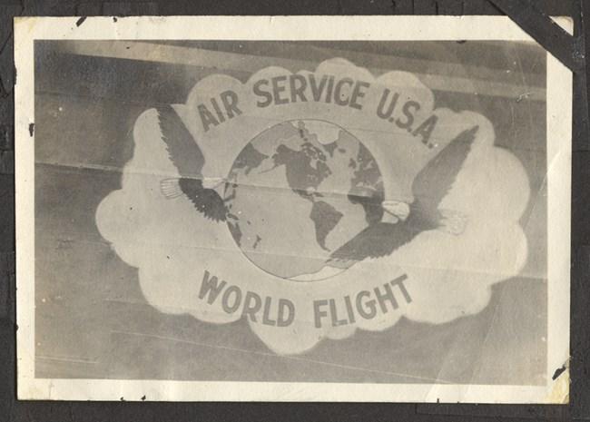 "Black and white photo of logo with a globe and two eagles. Text around the image reads ""Air Service U.S.A. World Flight"""