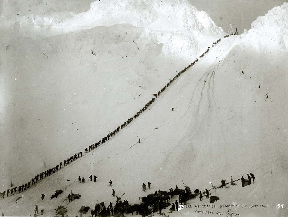 A historical photo of a line of stampeders climbing the Chilkoot trail in the winter.