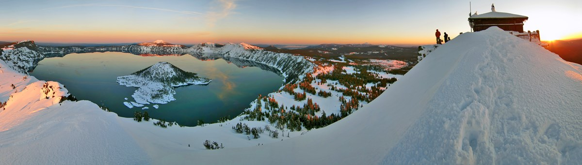 panoramic image of crater lake with snow
