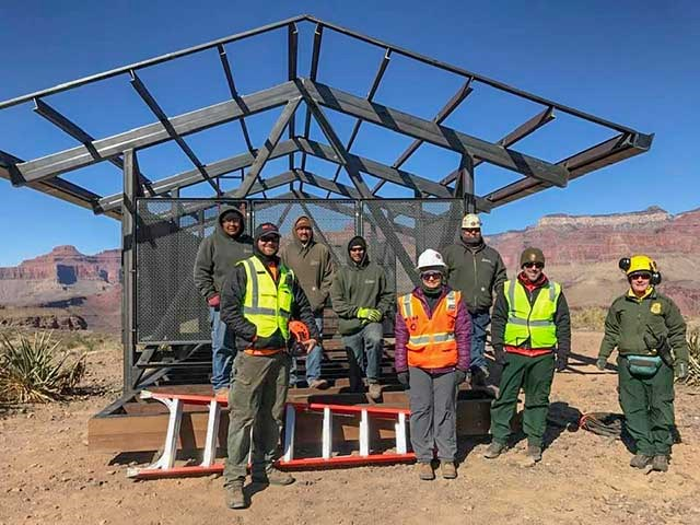 8 workers wearing safety vests and helmets are standing in front of the framework of a partially assembled shade structure 12 x 24 feet.