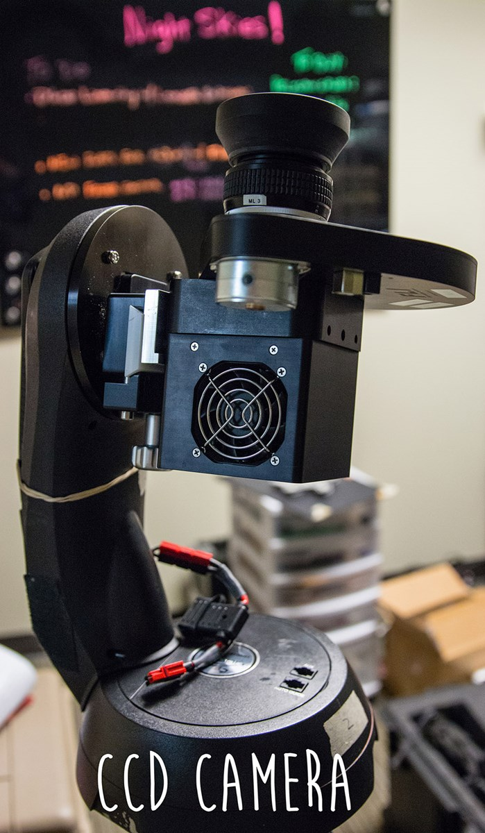 a teardrop shaped camera and a long oval robotic arm sit on top of a tripod