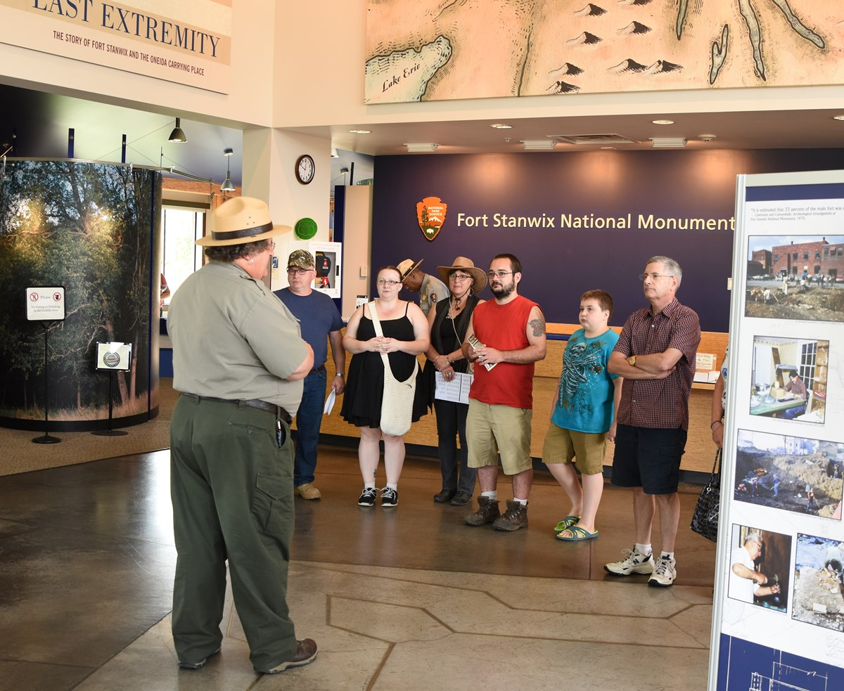 a park ranger stands in front of a colorful crowd at a visitor center, and points at a map.