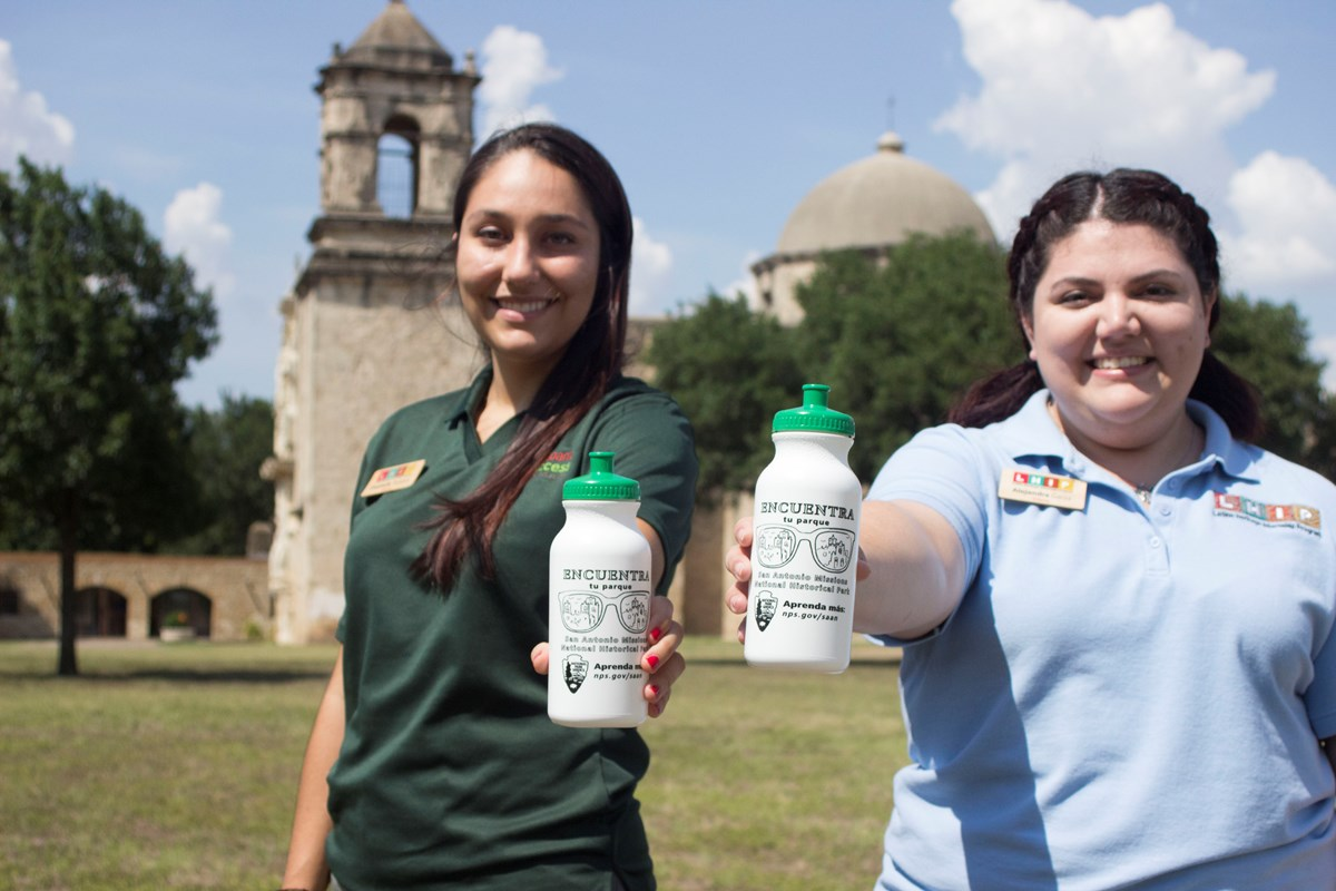 LHIP Intern and Community Outreach Fellow hold Latino Conservation Week water bottles