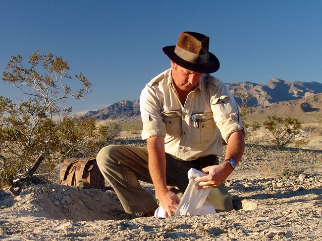 scientist working with fossils in the desert